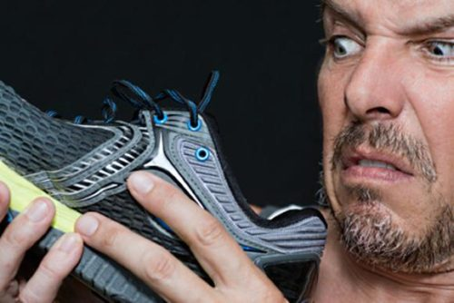Man discovering cat pee in a shoe (or that his socks smell real bad).