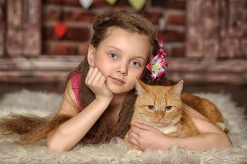 a child wit ha cat on the carpet